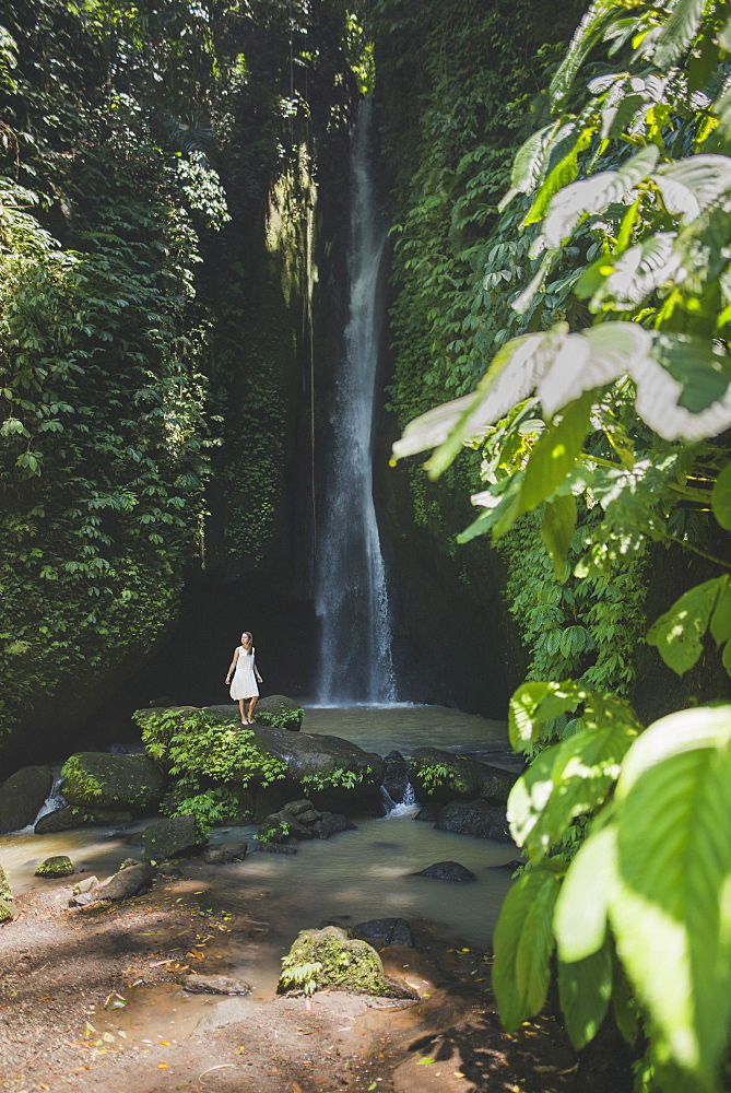 Woman by waterfall in Bali, Indonesia