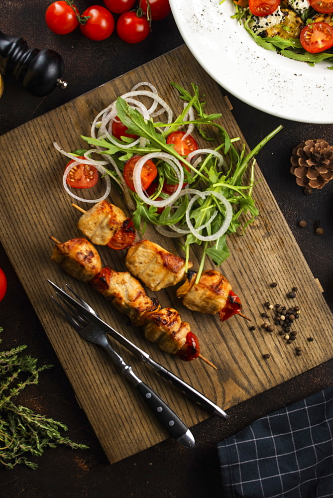 Grilled meat skewers and salad on cutting board
