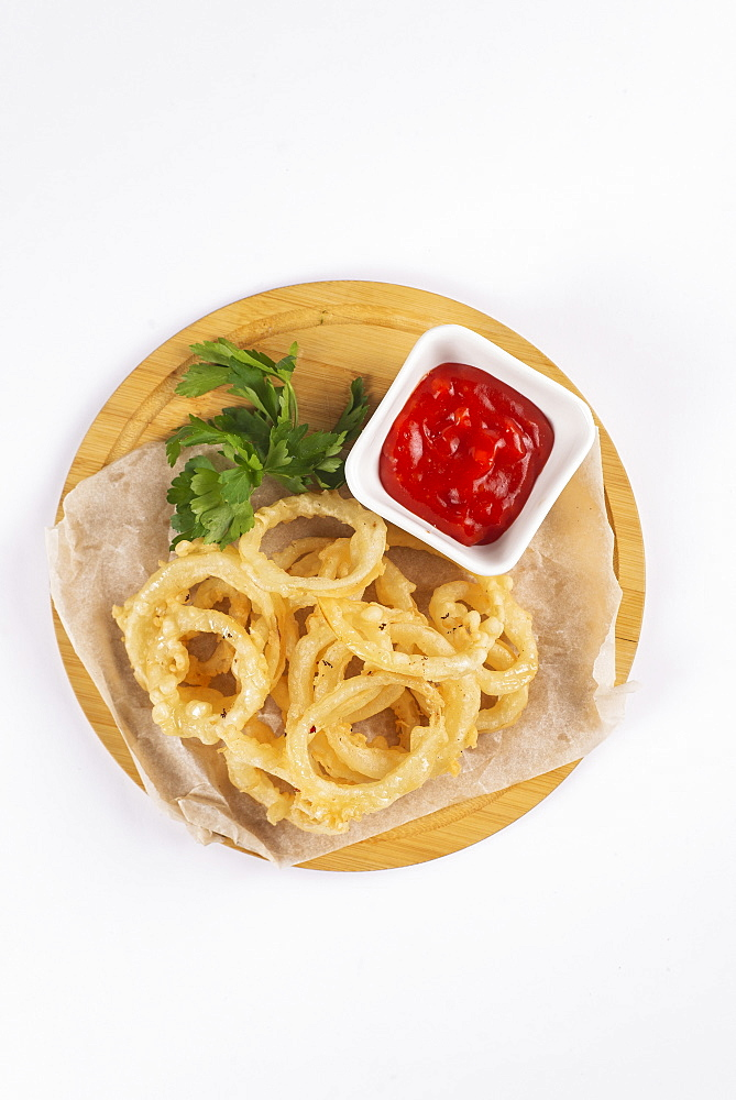 Onion rings with tomato sauce on cutting board