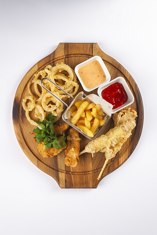 Deep fried snacks and sauce on cutting board