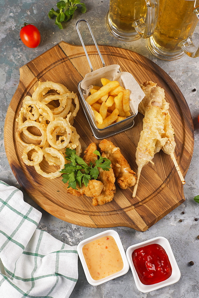 Deep fried snacks on cutting board with sauce
