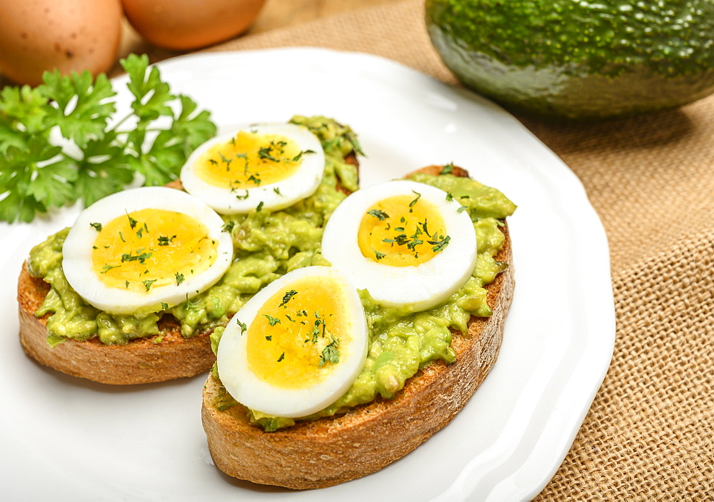 Avocado and egg on toast with parsley