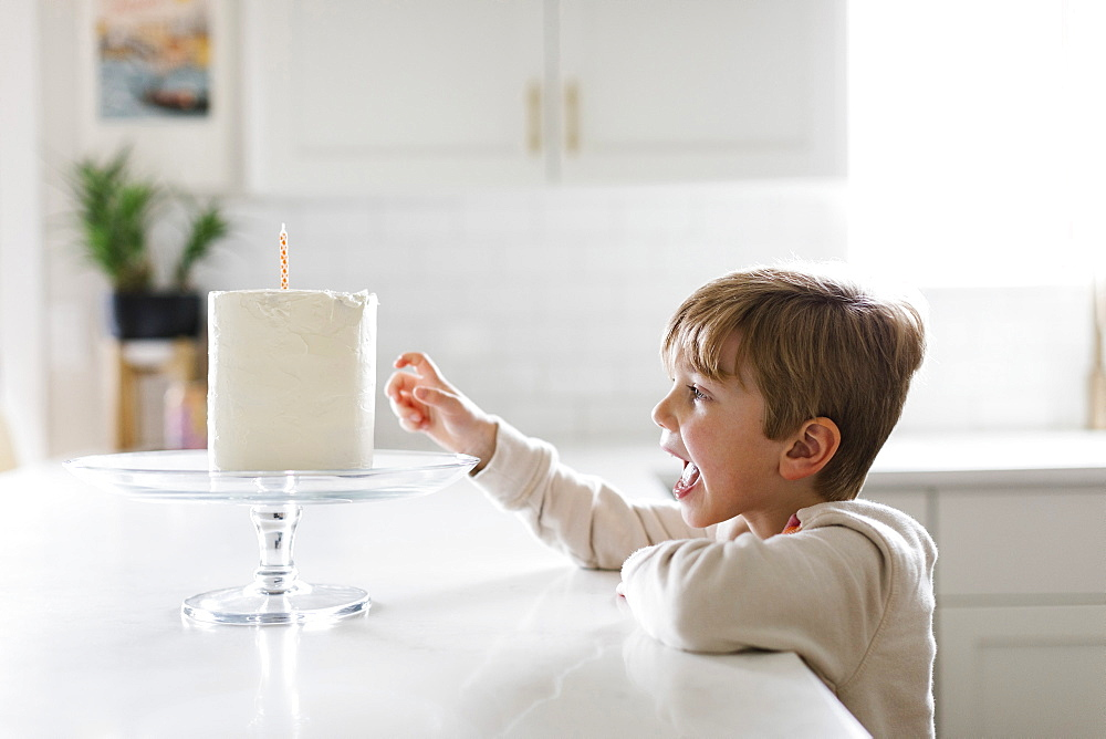Boy reaching for birthday cake