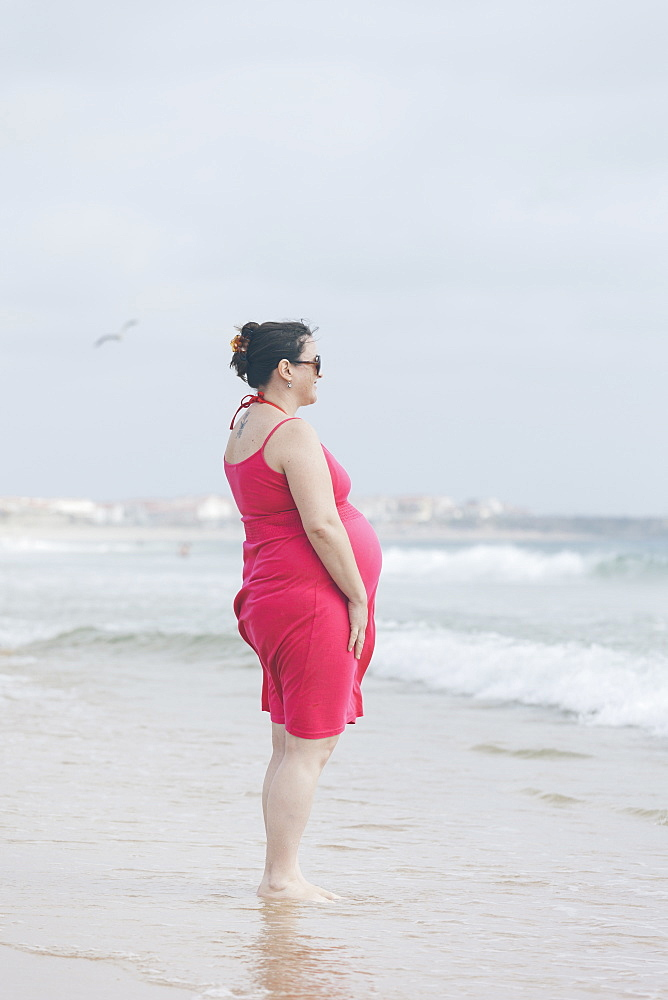 Pregnant woman wearing pink dress on beach