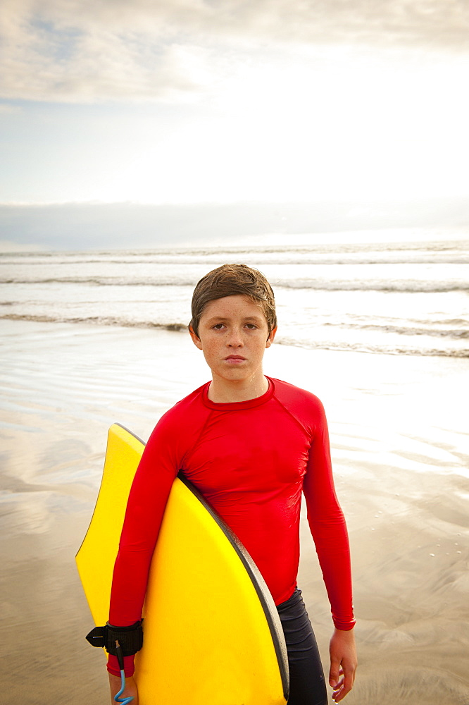 Boy holding body board on beach