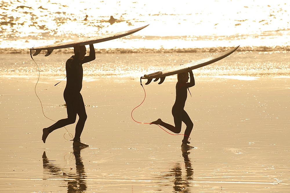 Father and son carrying surfboards on beach at sunset