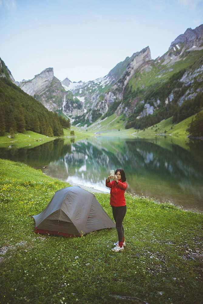Woman taking photograph by tent near Seealpsee lake in Appenzell Alps, Switzerland