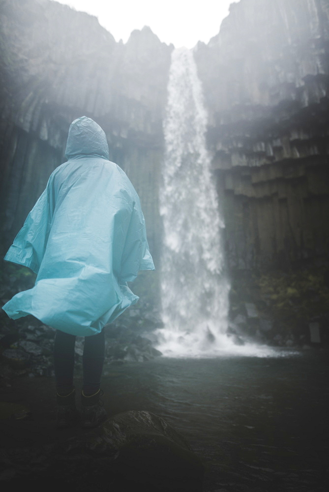 Woman wearing blue raincoat by waterfall in Skaftafell, Iceland