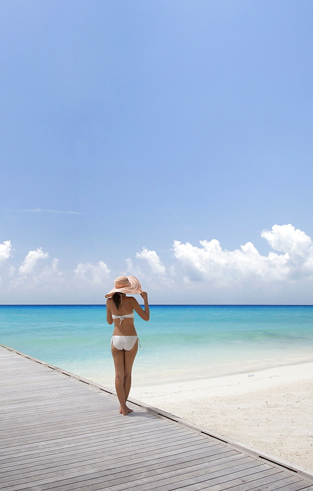 Woman wearing bikini by beach in South Male Atoll, Maldives, South Asia
