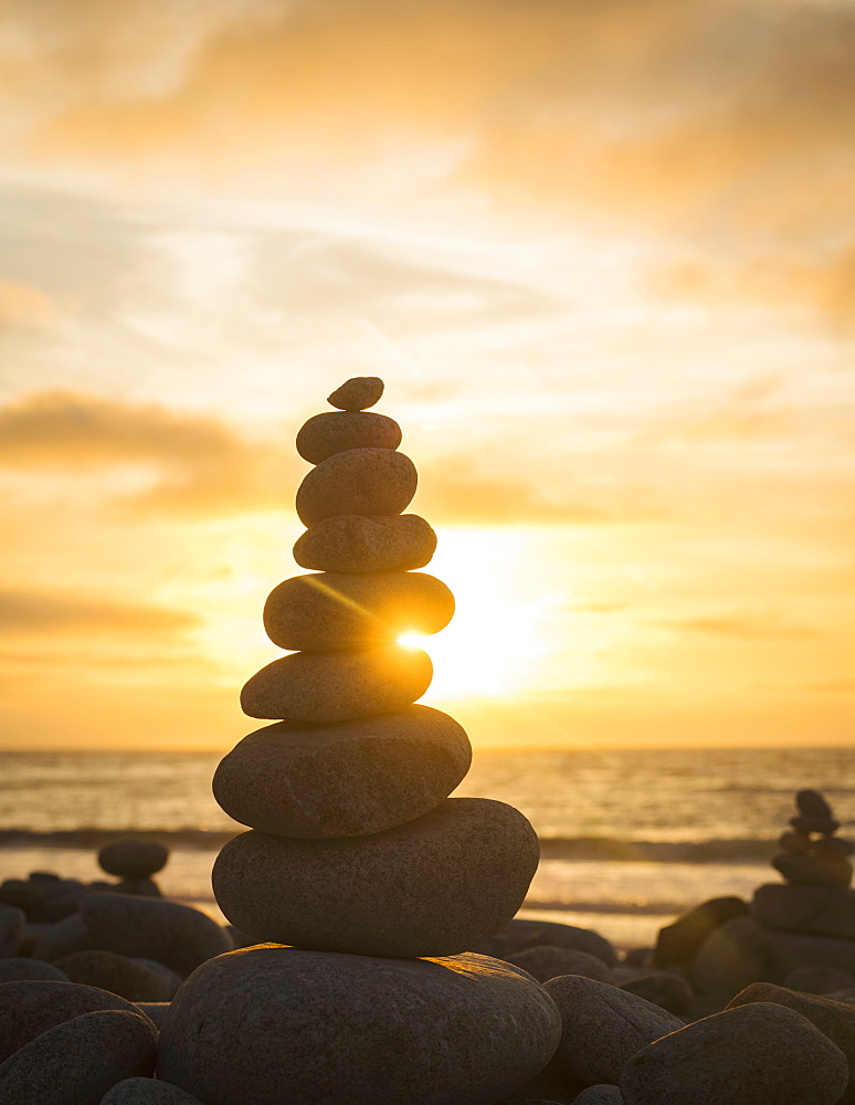 Stacked stones on beach at sunset