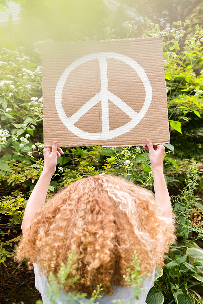 Girl holding sign with peace symbol