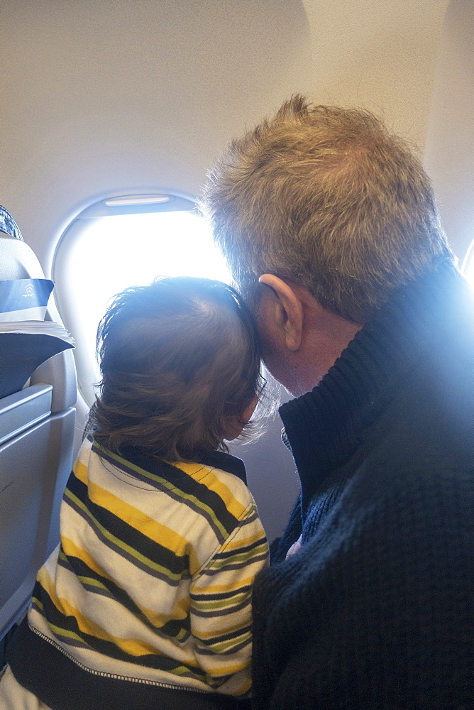 Man and child looking out airplane window