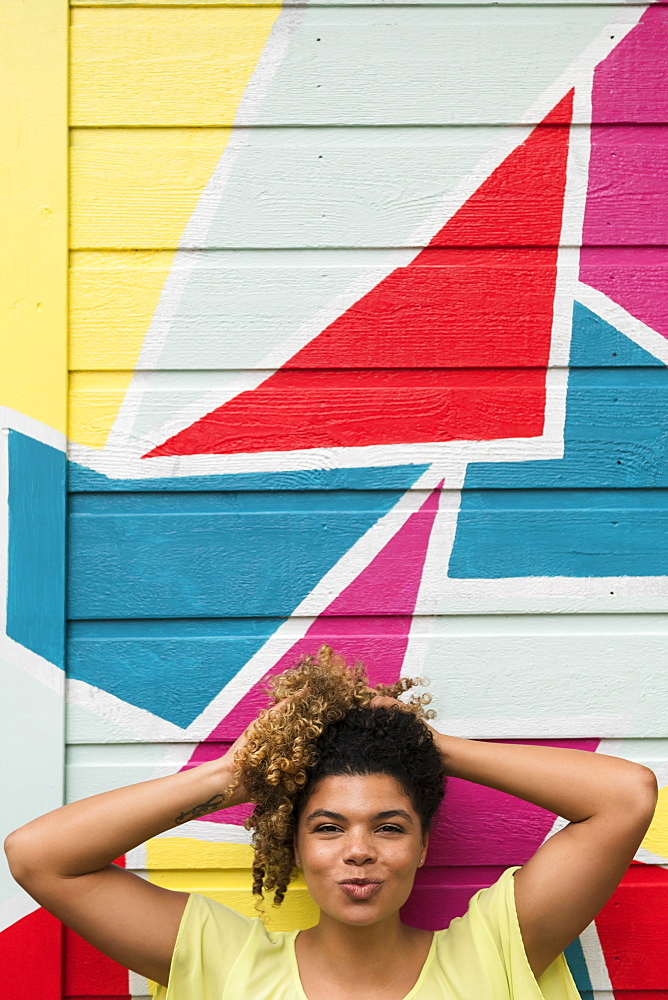 Woman posing against colorful wall