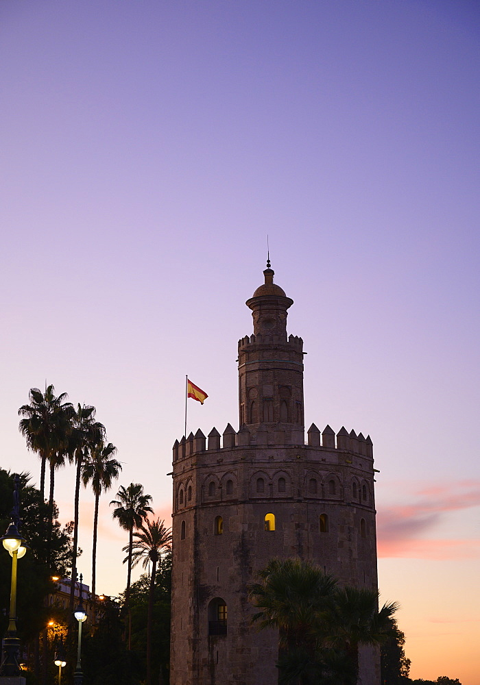 Torre del Oro by palm trees at sunset in Seville, Spain