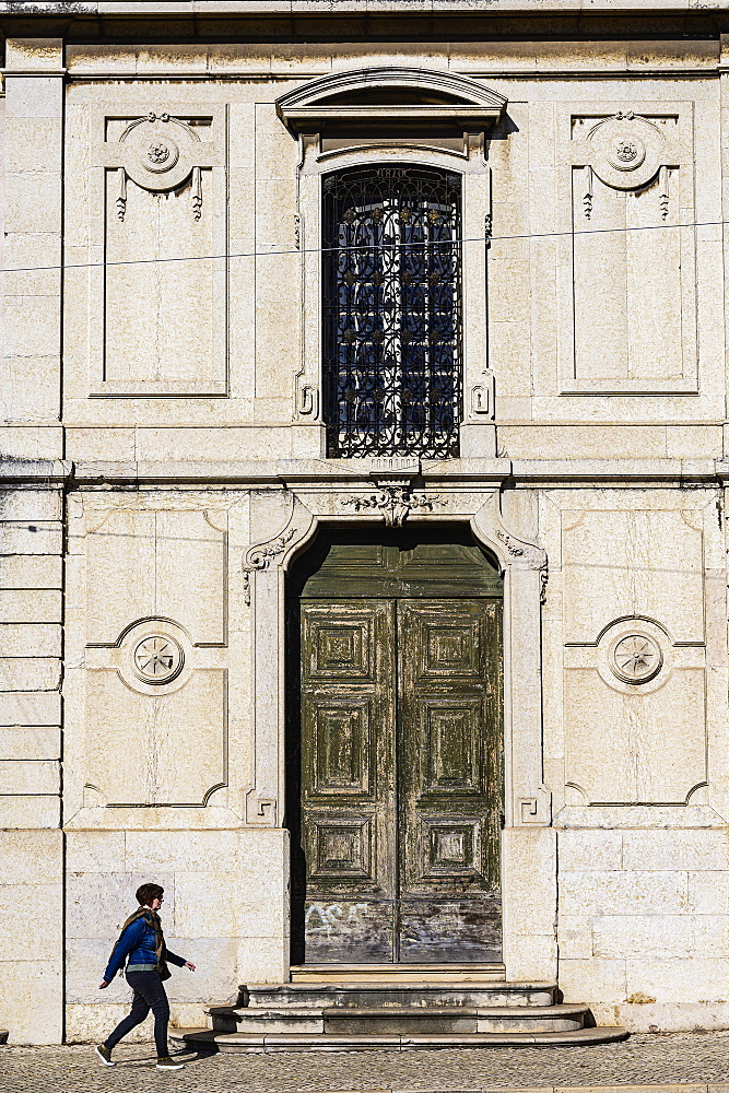 Woman walking past old building in Lisbon, Portugal