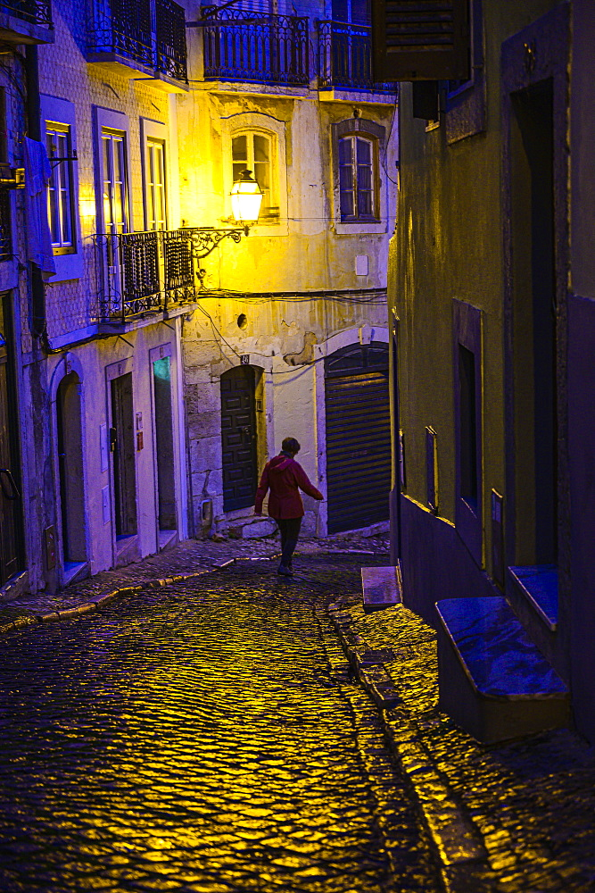 Woman walking in alley at night in Lisbon, Portugal