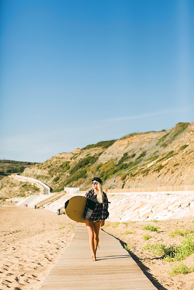 Woman holding surfboard on boardwalk