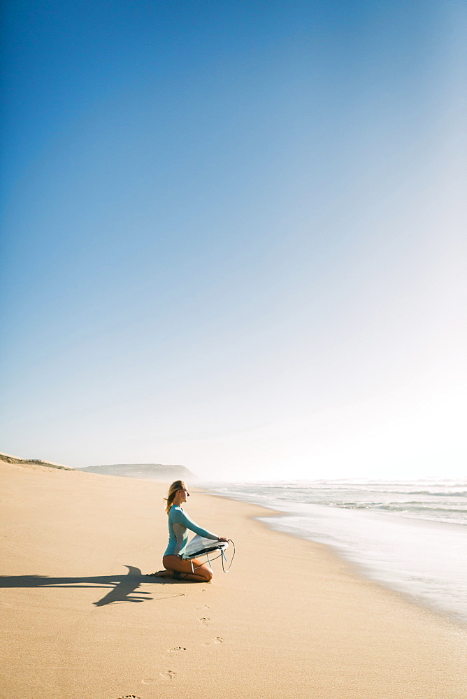 Woman kneeling holding surfboard on beach