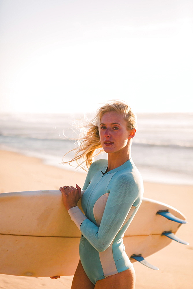 Woman wearing wetsuit holding surfboard on beach