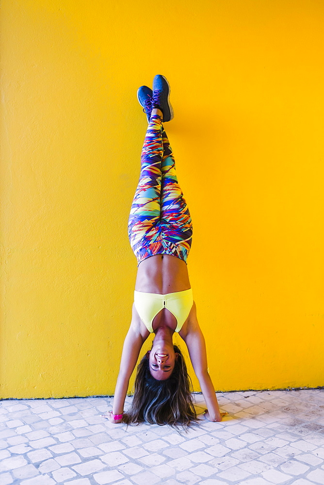 Smiling woman doing handstand by yellow wall