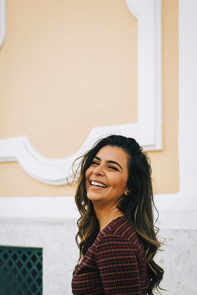 Smiling woman by wall, Lisboa, Lisbon, Portugal