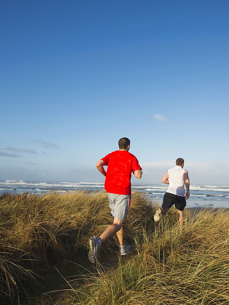 Young adult men running on dune, Rockaway Beach, Oregon