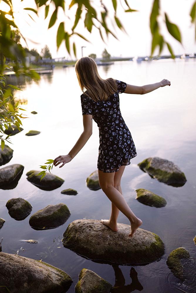 Woman balancing on rock in sea