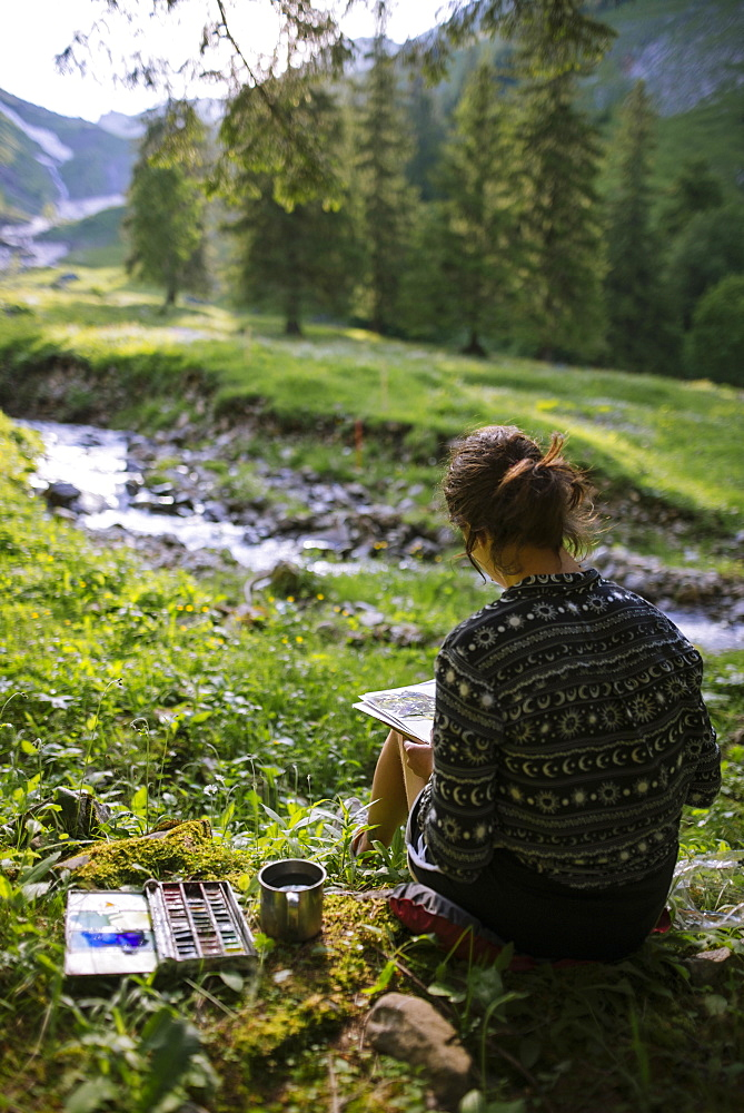 Woman painting with watercolors by river in Appenzell, Switzerland - 1178-28410