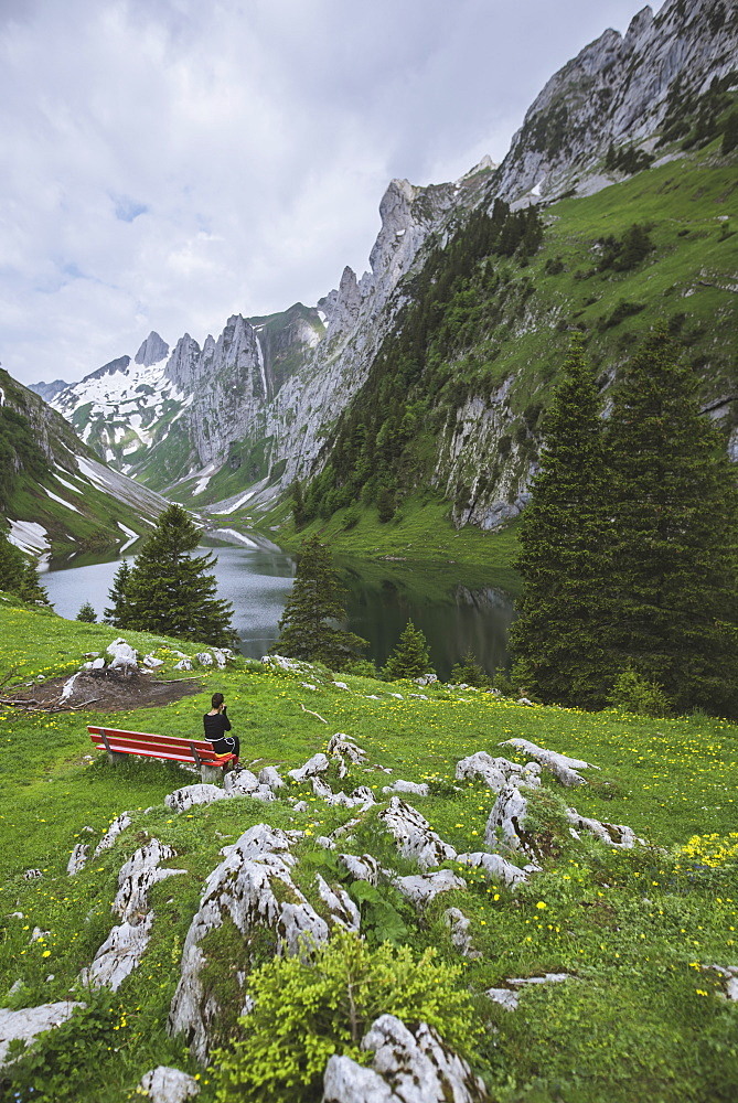 Woman sitting on bench by mountains in Appenzell, Switzerland