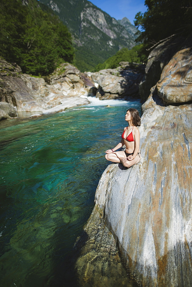Woman wearing bikini sitting on rock by river