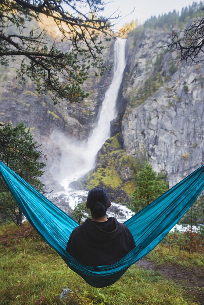 Young man resting in hammock by waterfall