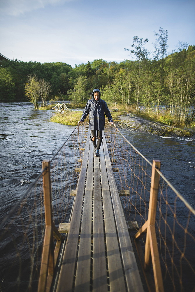 Young man walking over wooden bridge