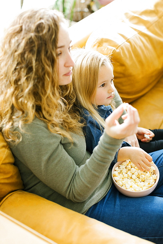 Mother and daughter with bowl of popcorn watching movie