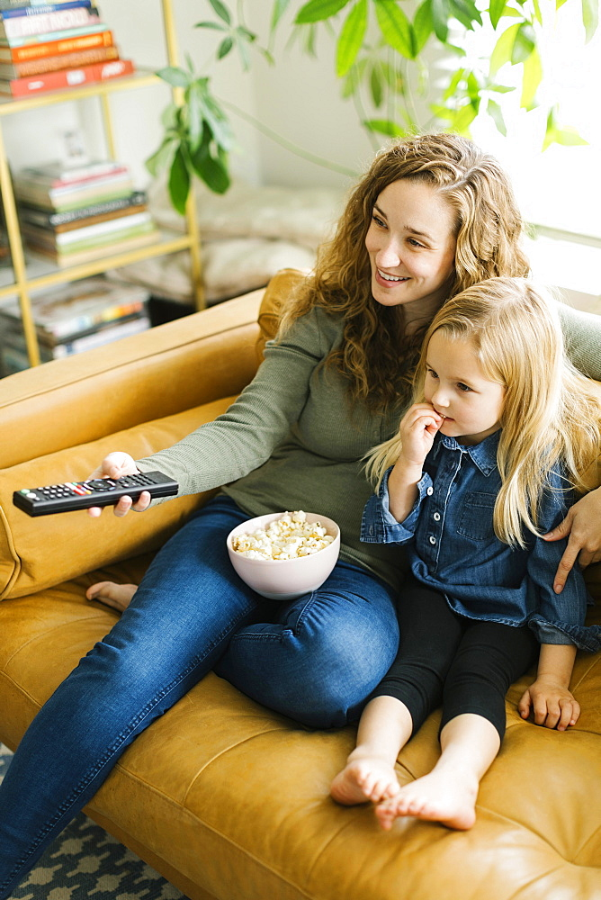 Mother and daughter with bowl of popcorn watching movie - 1178-28611