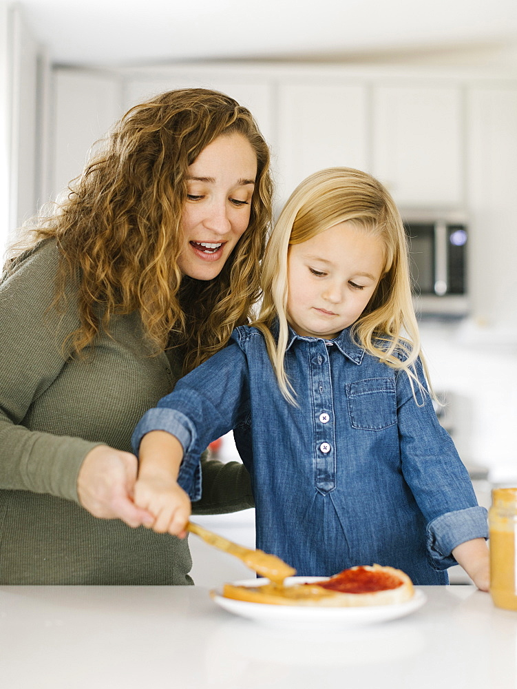 Woman making peanut butter and jelly sandwich with her daughter