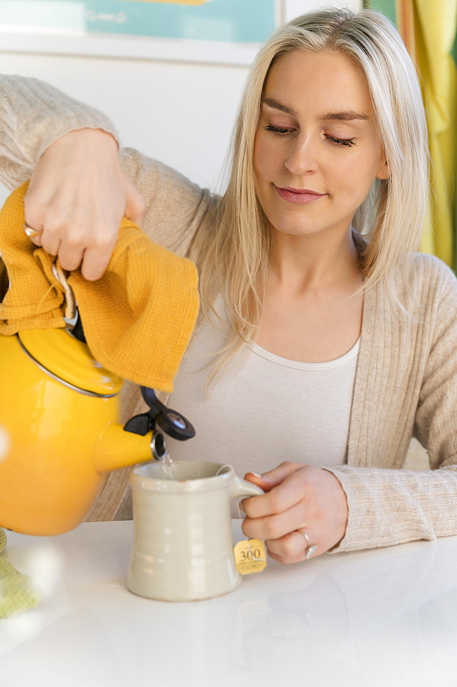Woman making tea, pouring water from kettle
