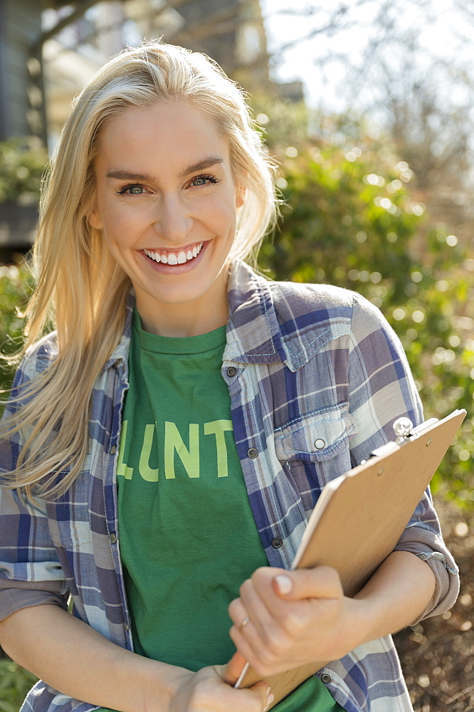 Smiling woman holding clipboard