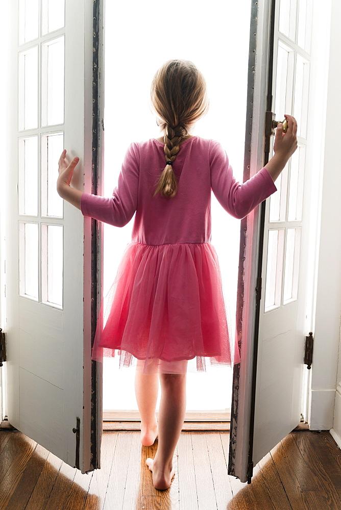 Rear view of girl (6-7) walking through doorway into light