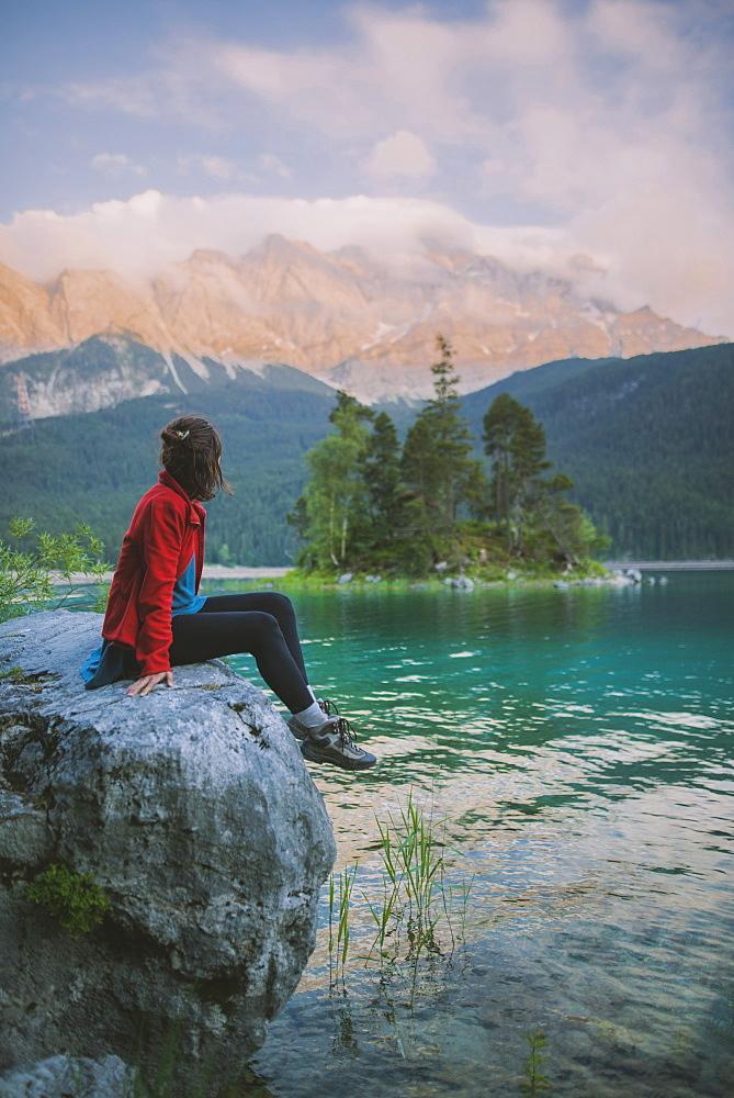 Germany, Bavaria, Eibsee, Young woman sitting on rock and looking at scenic view byEibseelake in Bavarian Alps