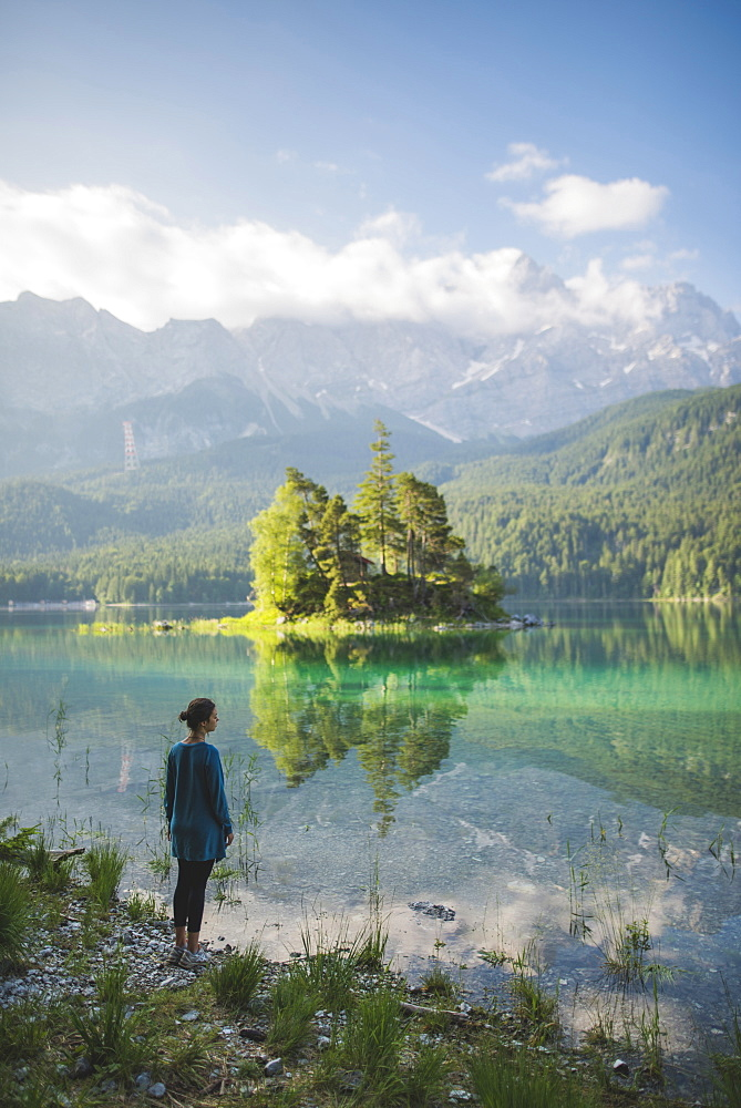 Germany, Bavaria, Eibsee, Young woman standing at shore ofEibseelake in Bavarian Alps