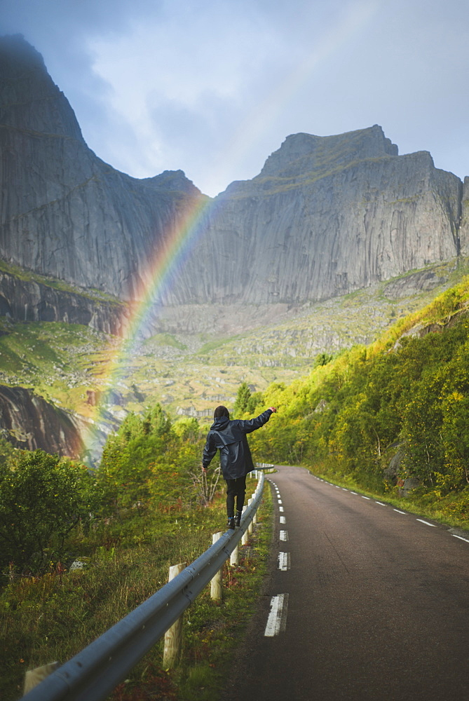 Norway, Lofoten Islands, Man balancing on crash barrier with mountains and rainbow in background