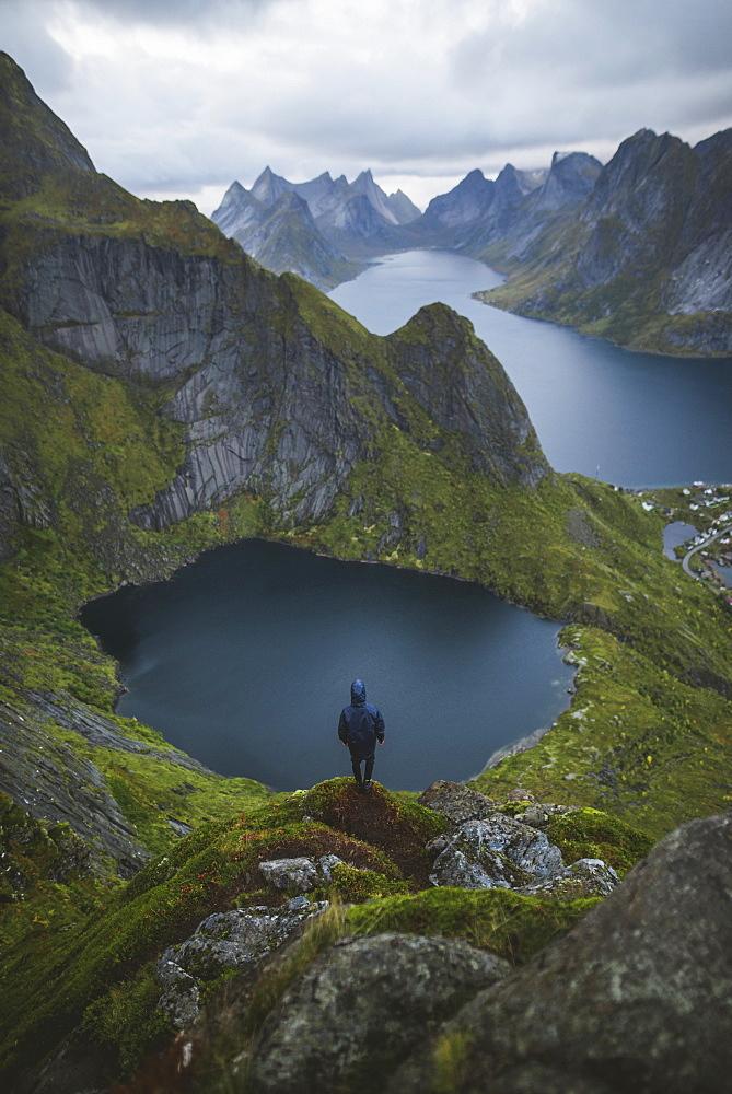 Norway, Lofoten Islands, Reine, Man looking at view fromReinebringenmountain