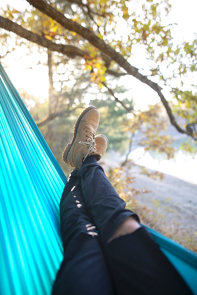 Italy, Man lying in hammock near lake