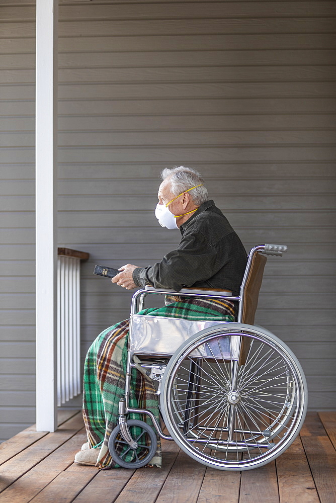 Senior man in wheelchair wearing protective mask to preventcoronavirustransmission on porch