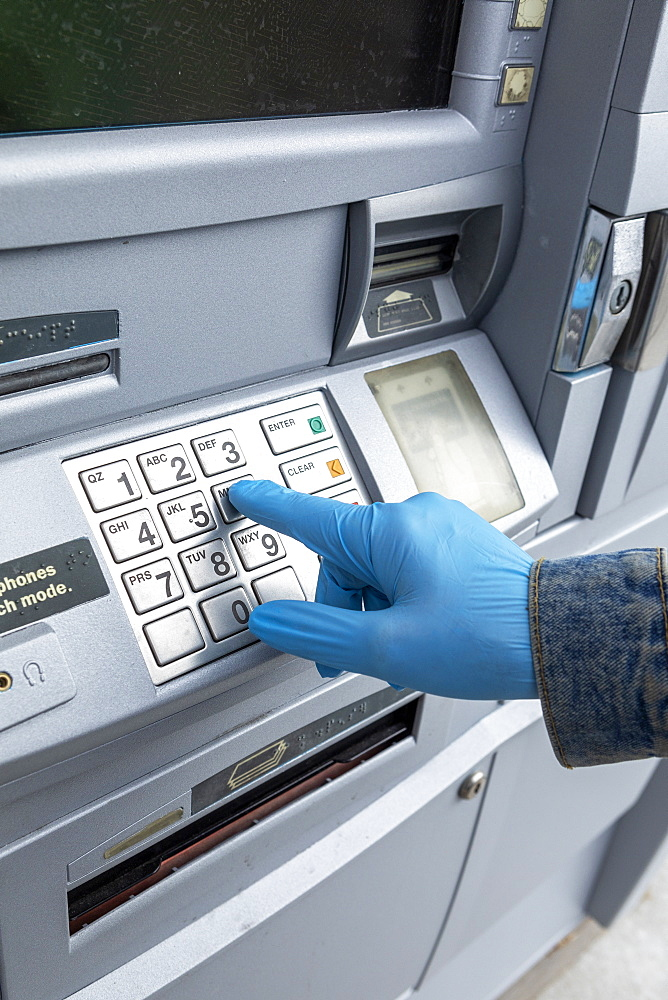 Close-up ofgloved hand on keypad of ATM machine