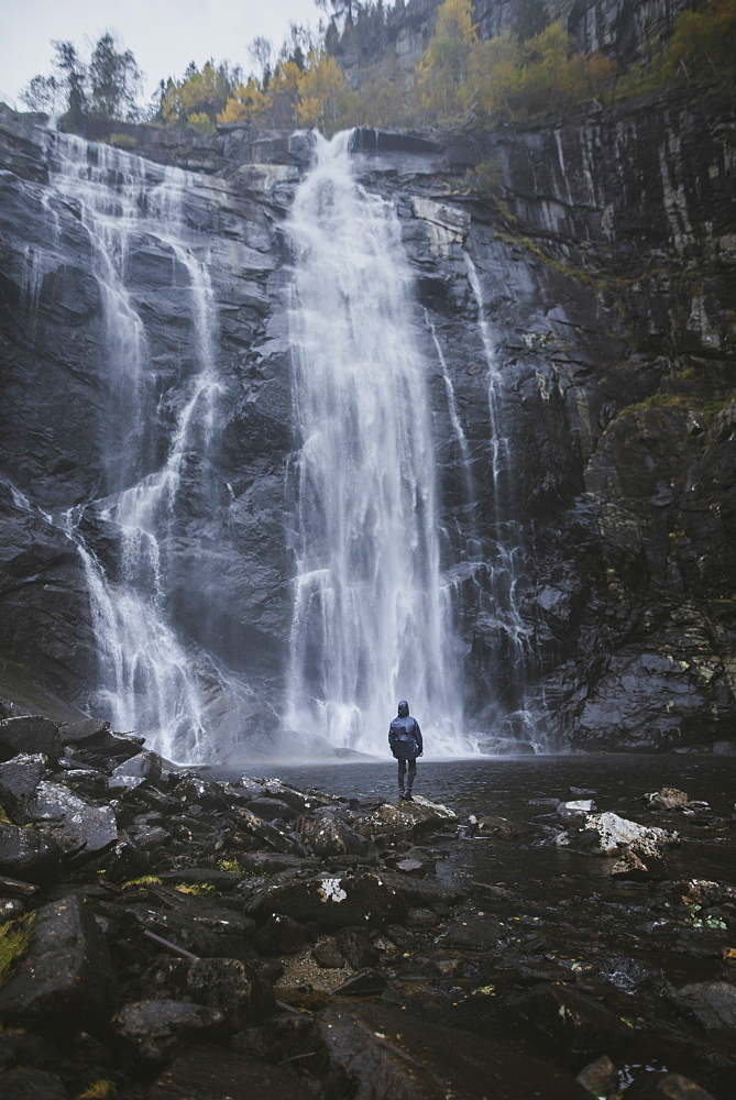Man standing by Skjervefossen waterfall in Norway