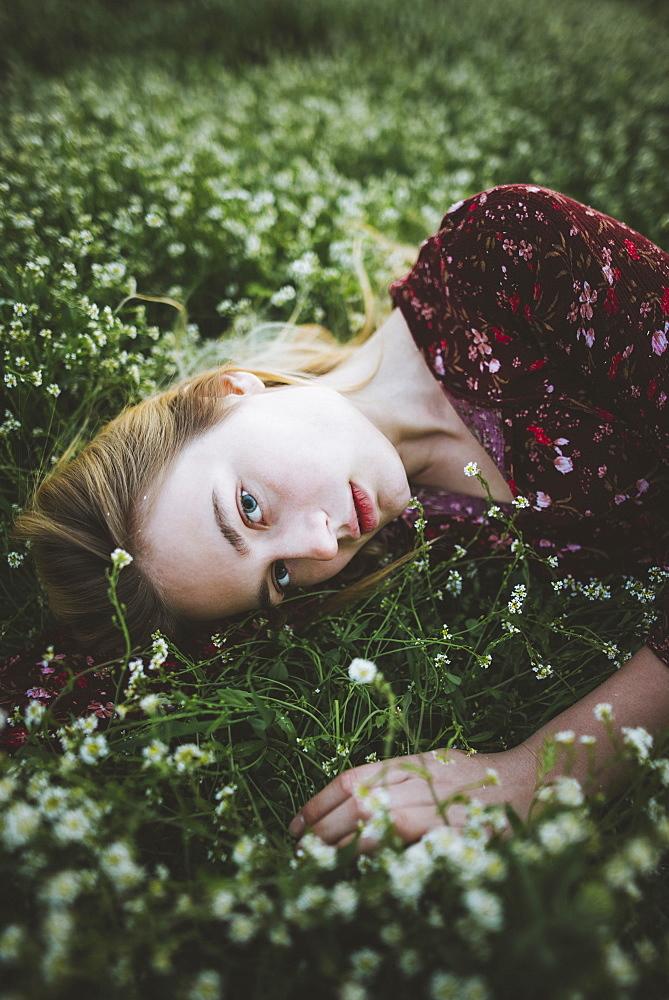 Woman wearing blouse lying in meadow