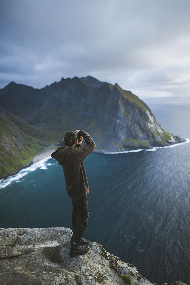 Man taking photograph on cliff at Ryten mountain in Lofoten Islands, Norway