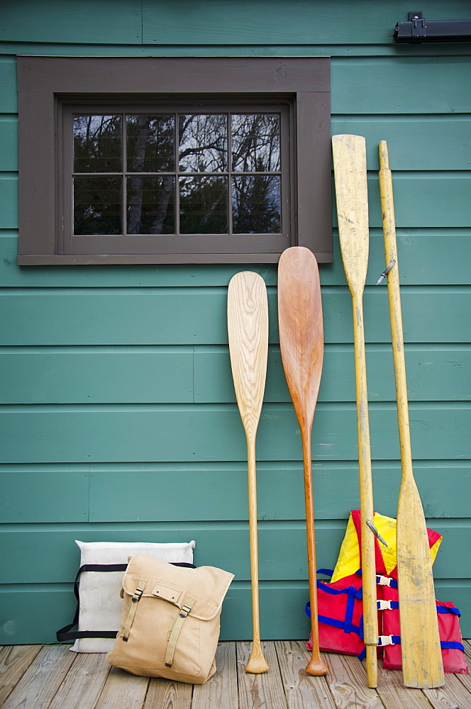 Oars and life jackets by blue wall