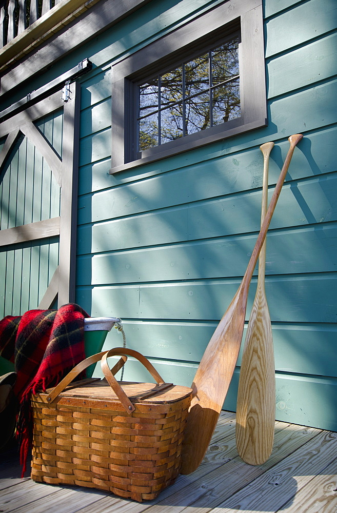 Oars and picnic supplies by blue wall